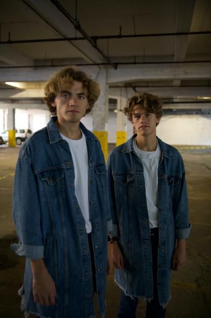 Two light-skinned blonde men in denim shirts standing in parking garage.