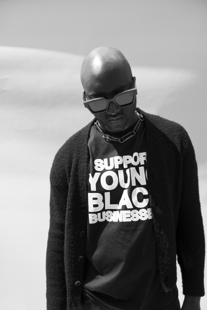 """Black-and-white portrait of Virgil Abloh, an African-American man looking down wearing sunglasses with a cardigan over a t-shirt that reads """"SUPPORT YOUNG BLACK BUSINESSES."""""""