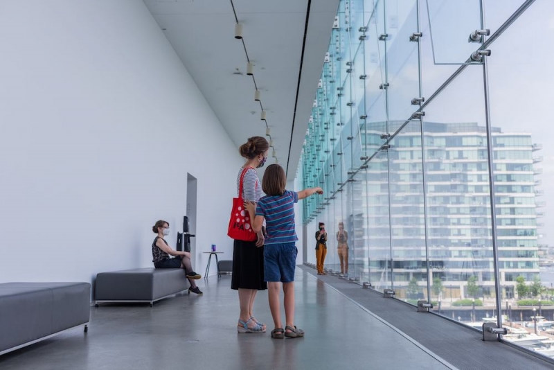A school-age child and his mother look out of a wall of windows in the ICA's Founders Gallery. The boy points.