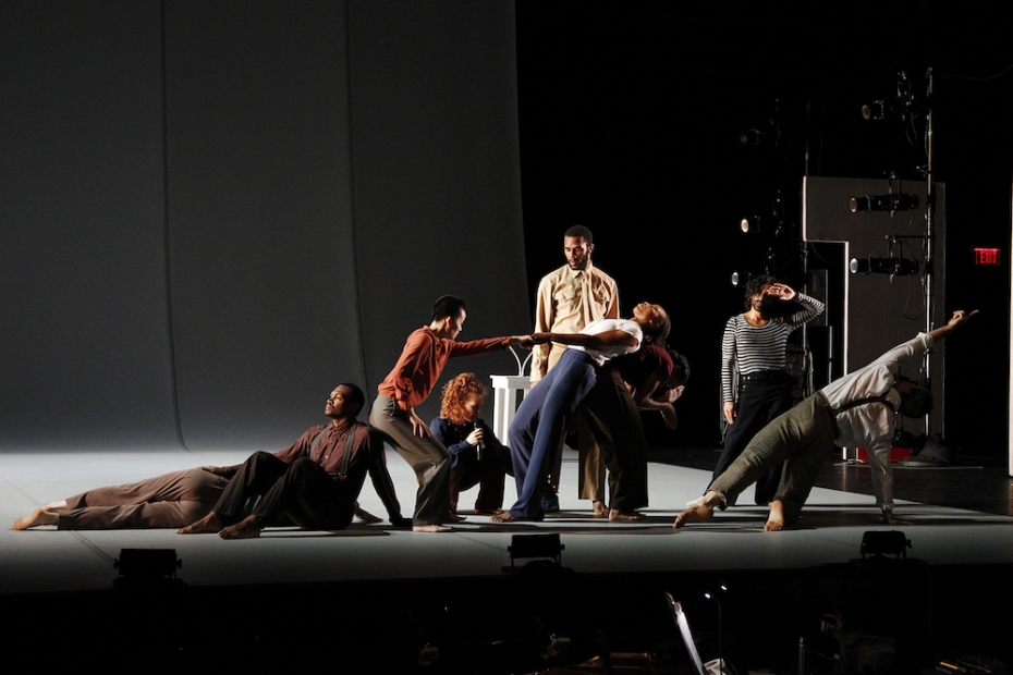 Nine dancers in plain, old-fashioned looking streetwear are posed across a dimly lit stage, some lying, some sitting, some standing.
