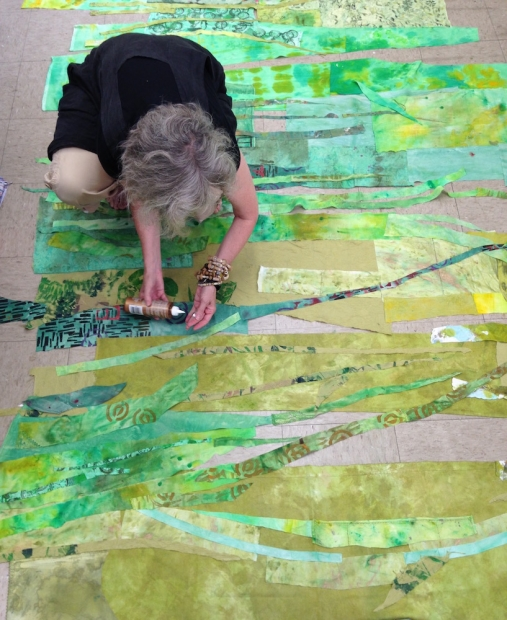 Fiber artist Merill Comeau kneeled down in her studio; she is putting glue in her hands and putting together strands of green cut-fabric to create a large scale collage.