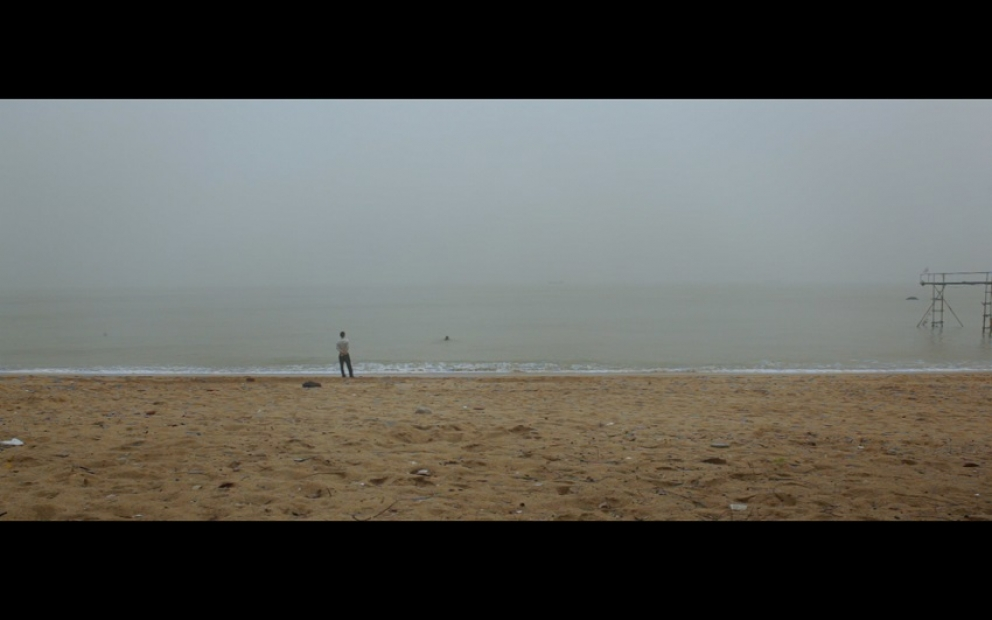 Landscape view of a misty and grey sea meeting tan sand. Off-center to the left, a figure stands at the very edge facing the water.