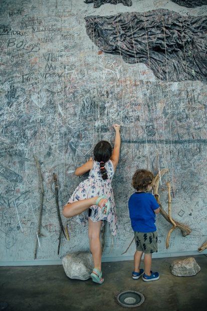 Children using long sticks to draw on the ICA art wall.