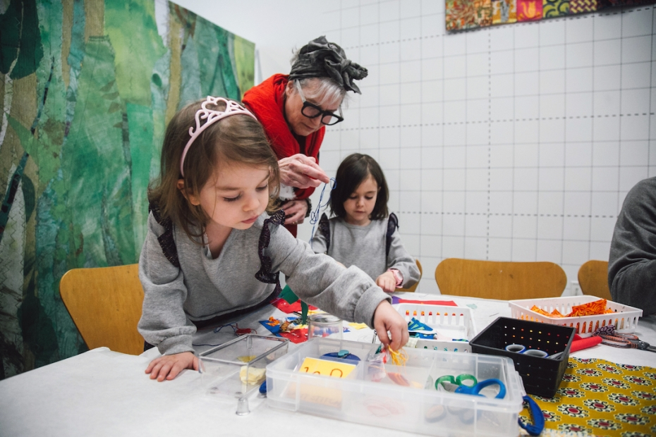 Two young girls in matching sweatshirts make art with artist Merill Comeau, who wears large glasses, a red scarf, and a cloth tied around her gray hair.