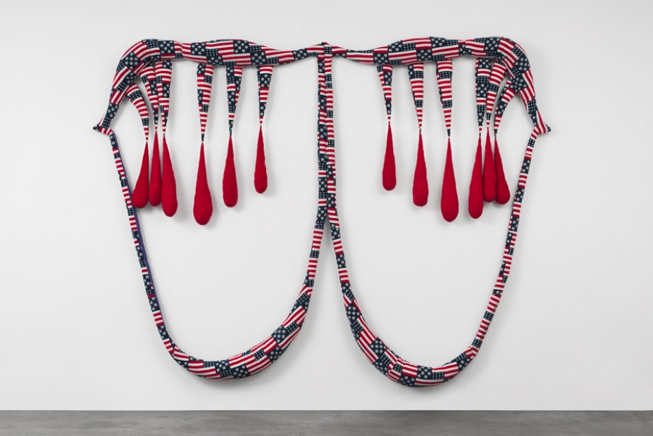 A soft sculpture that looks like a mouth with blood dripping with patterns of stars and stripes.