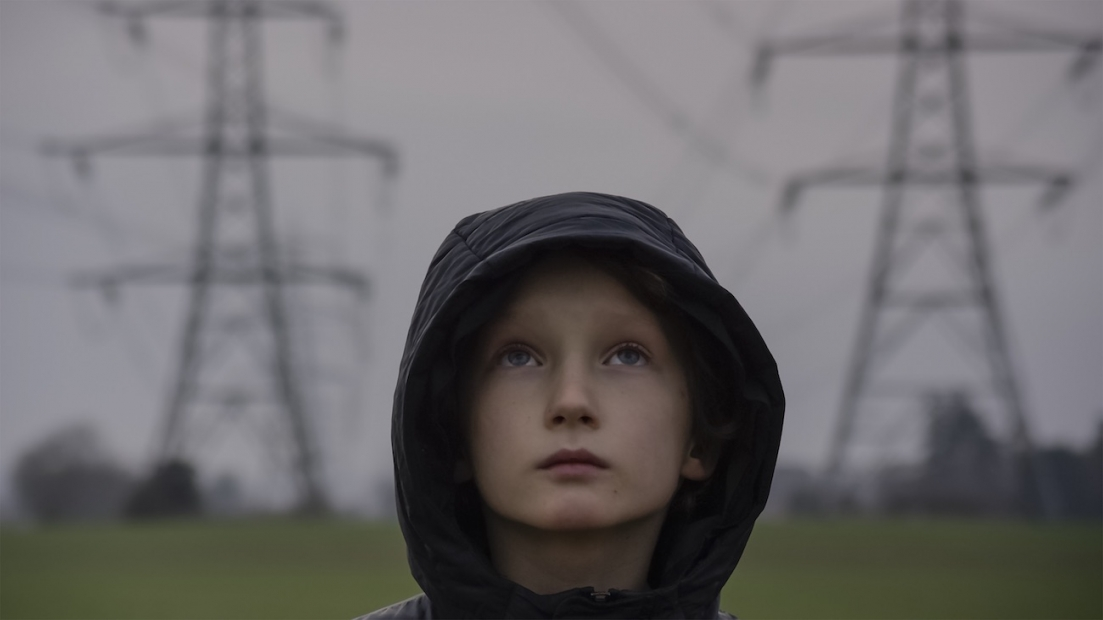 A film still shows a boy of about 9 or 10 in a hoodie facing the camera but looking to the sky. Behind him are two TV towers.
