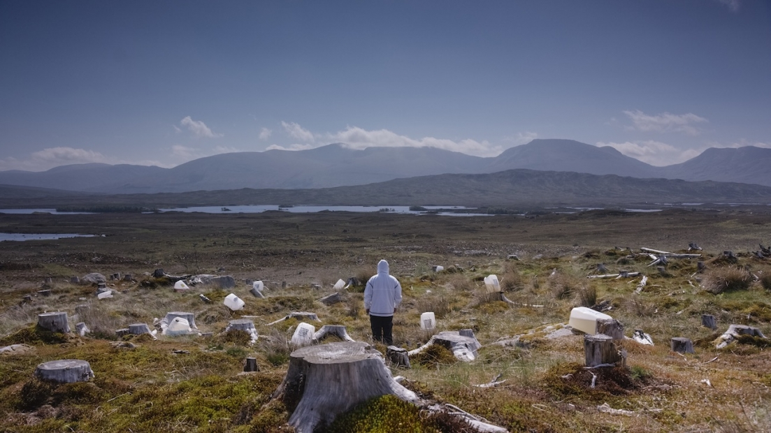 A film still shows a mountainous landscape. In the foreground stands a figure looking away, among dozens of cut-down-tree stumps and large plastic containers of liquid.