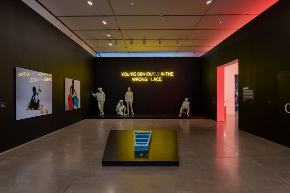 """A gallery with a light blue ladder laying on a black plinth, a black wall with the text """"You are obviously in the wrong place"""" behind several light blue mannequins, and several large photos on the side walls."""