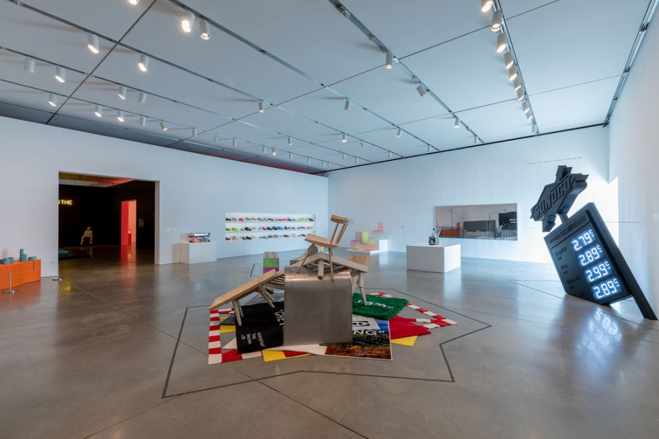 A gallery with a heap of rugs and furniture in the middle, a sculpture resembling a tilted all-black gas station sign on the right, and three shelves of sneakers in the background.
