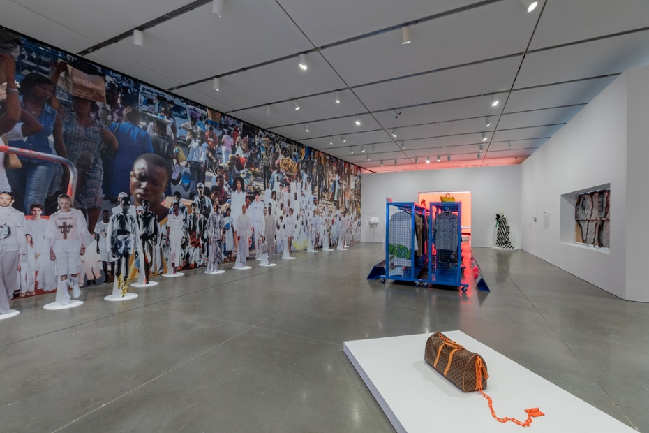 A gallery with a wall-sized photo collage of an African street scene and dozens of models in all white, with standing model cutouts in front, racks of clothing, and a Louis Vuitton bag bound to a plinth by a neon orange chain.