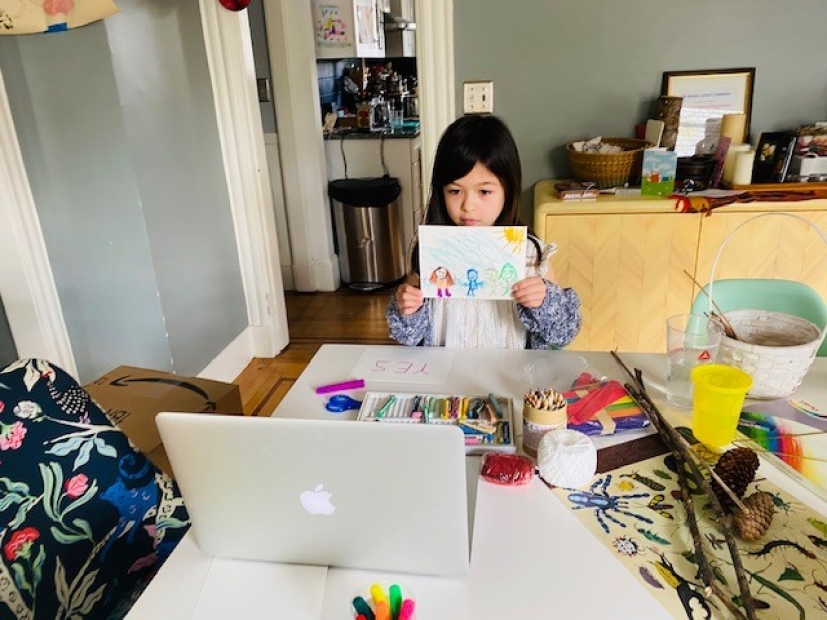 A young child holding up a crayon drawing to show on her laptop over a table full of colorful art supplies.