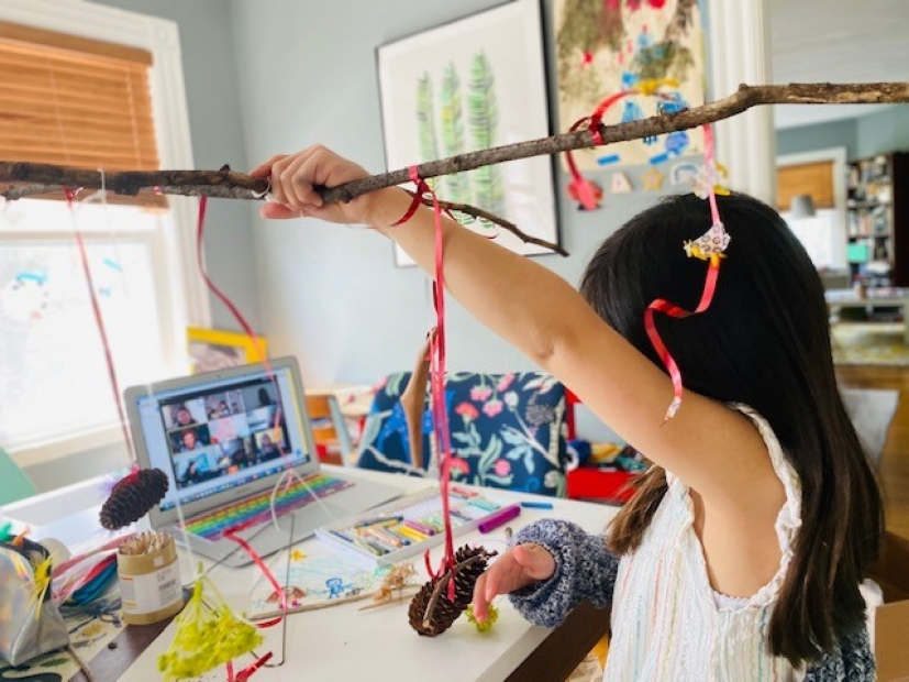 A young child raises a wood stick decorated with colorful streamers as she participates in a virtual workshop on her laptop.