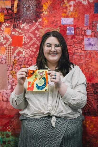 A visitor holding up her quilt square creation in front of a red-patterned tapestry background wall.