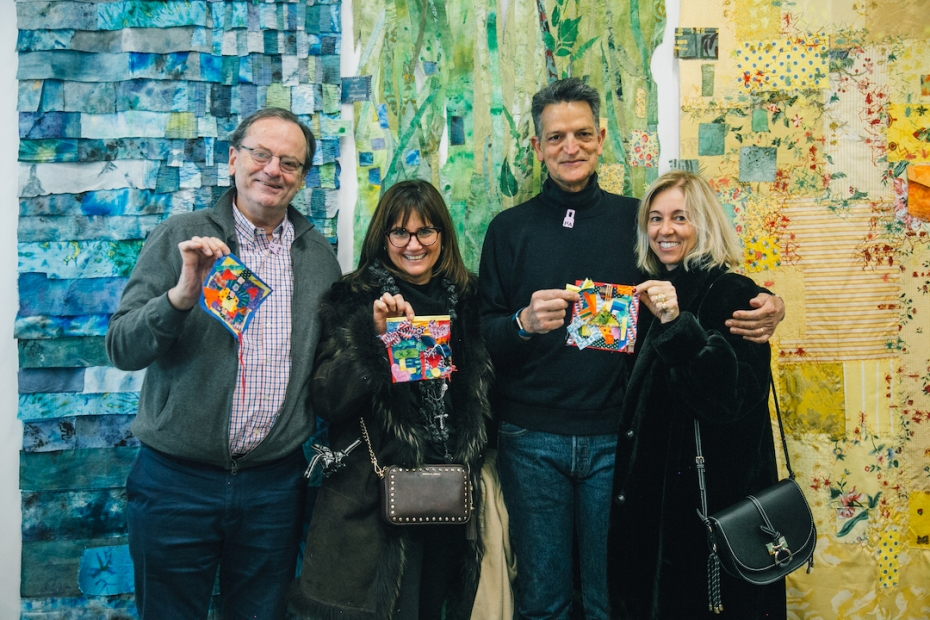 A group of four adult visitors holding up their quilt square creations in front of a colorful, patterned tapestry background wall.