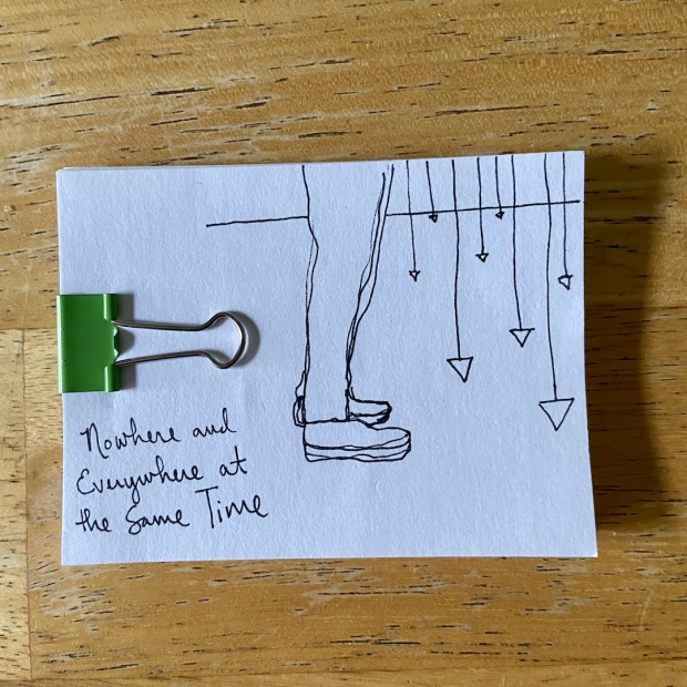 A drawing of legs standing before a series of hanging pendulums on a white index card with a green binder clip.