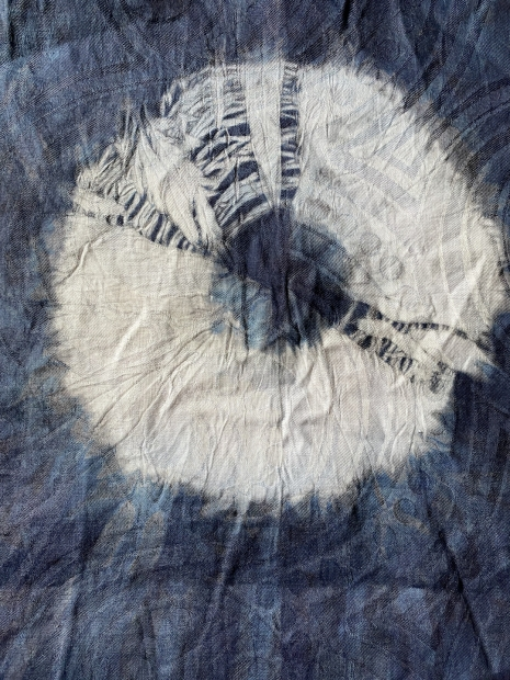 Faded blue fabric with white circular dyed design in the center