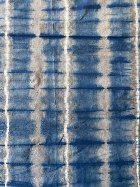 Light fabric with gridded, vibrating dyed design in a blue colored dye
