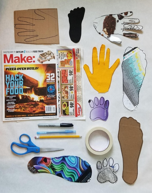 Cut-outs from colorful magazine layouts of handprints, footprints, and paw prints from a cat.