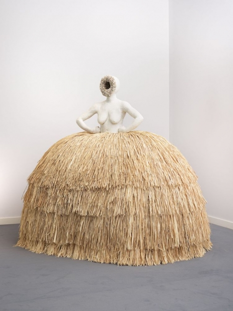 A sculpture by Simone Leigh of a woman with a raffia skirt.