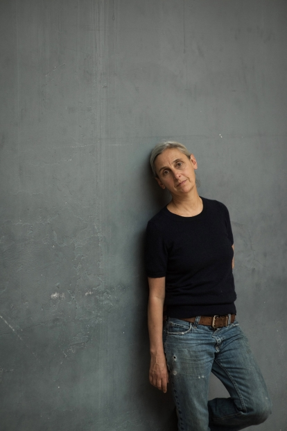 Anne Teresa De Keersmaeker, in a black top and blue jeans, leans against a gray wall.