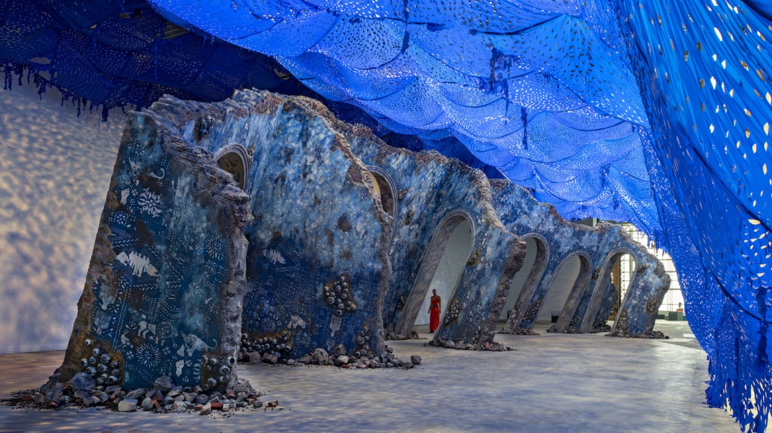 A woman in a red dress walks among a sculpture resembling an architectural ruin inside an industrial-style building. A bright blue perforated canopy creates a light-dappled effect on the floor and walls.