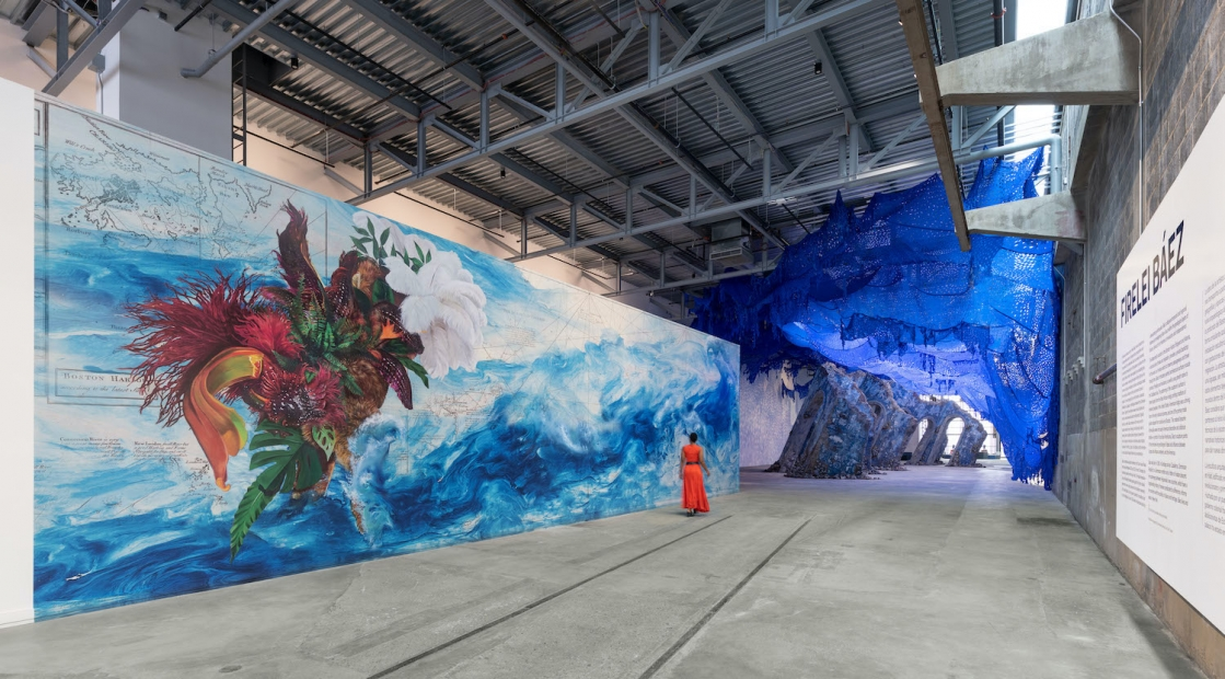 """A woman in a red dress walks along a monumental mural in a large industrial building and toward a sculpture resembling an architectual ruin. At left is wall text headed with """"Firelei Báez."""""""