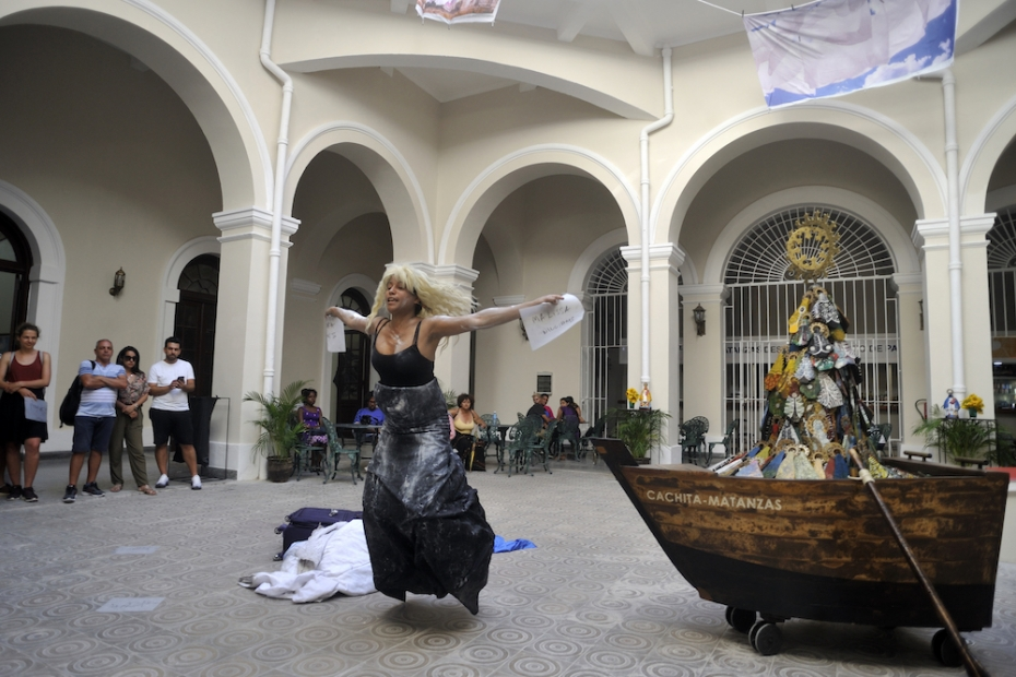 A medium-skinned woman wearing a blond wig performs in a courtyard. Her outstretched arms hold pieces of white paper with writing on them and she is jumping. A suitcase and blanket are behind her. About a dozen seated and standing spectators watch.