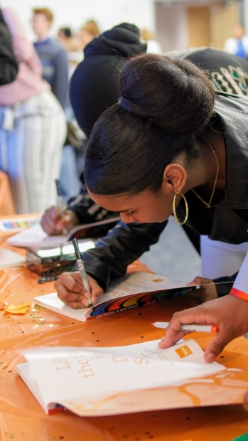 A photo shows two young women intently signing books.