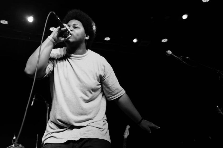 A black and white photo shows a young man performing on stage, holding a microphone, against a black background.