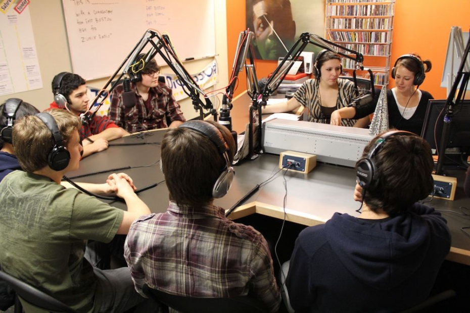 Eight young people wearing headphones gather around a series of microphones and a sound board in a radio studio.