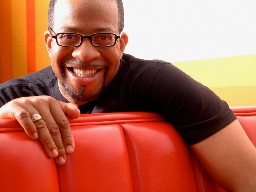 Man with glasses and medium dark skin tone smiles, draped over diner-style seat
