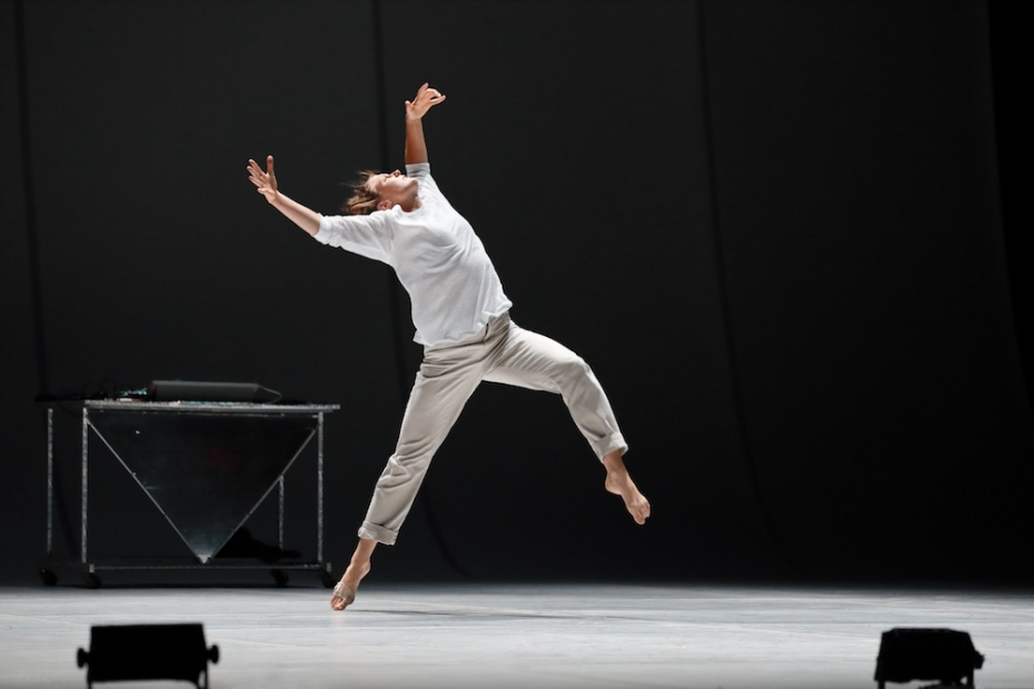 A man in a light shirt and pants seems to be caught mid-leap on a stage with a white floor and a black background