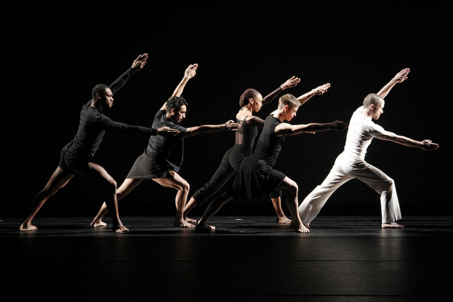 Four dancers in black and one in white lunge to the right with outstretched arms on a dark stage.