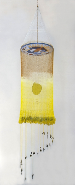 "A form that looks like a mobile or a fishing net with orange and yellow fibers hangs suspended. The net hangs from a white disc with a hand-drawn, mermaidlike figure and the words ""Rios vivos, pueblos libres"" (living rivers, free people)."