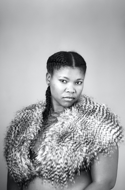 A black-and-white bust-length photograph of a person wearing a feathery capelet and beaded necklaces