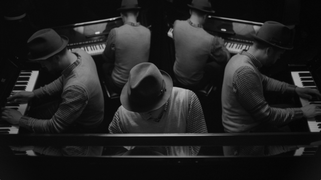 A black and white photographic image shows five men playing piano, facing away from each other, in an image that appears to be reflected.