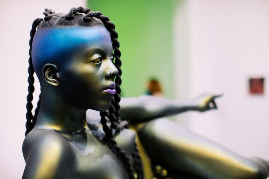 A sculpture that looks like a bronze but with, darker, more matte, and with iridescent tones depicts a reclining figure with braids, a nose ring, and purple lipstick. One arm is extended over the body, away from the camera.