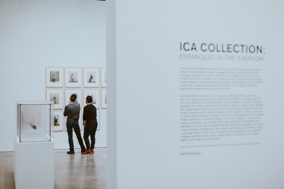 A view through a doorway shows two men looking at a wall of framed photographs from behind. In the foreground is a wall with text that says ICA Collection.