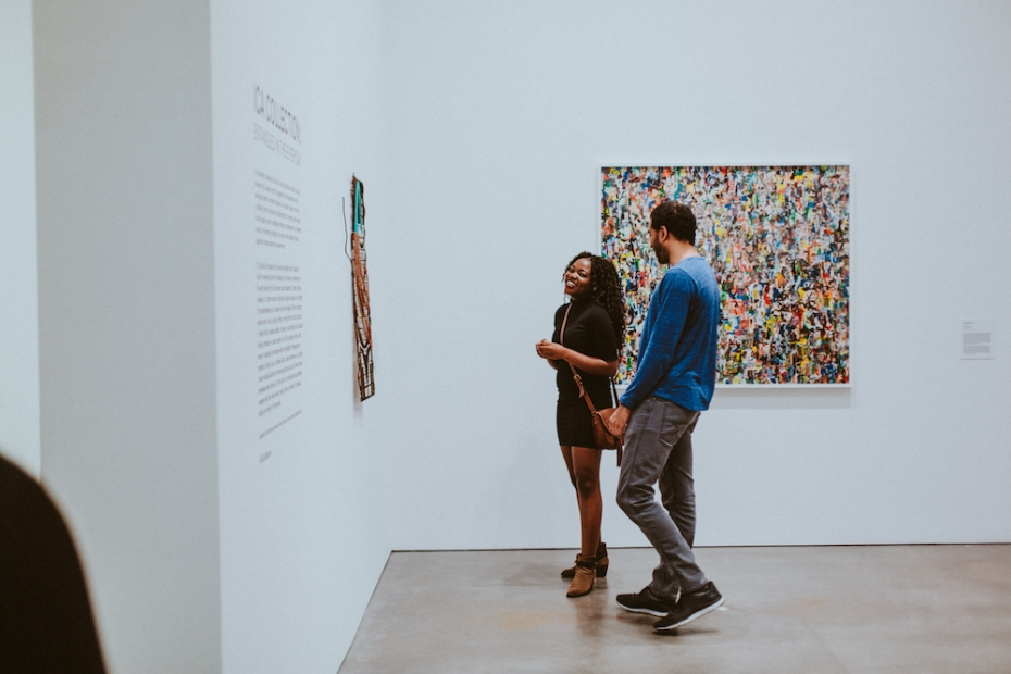 A man and woman look toward the left, at an artwork on the wall. She is smiling. A colorful square artwork is behind them.