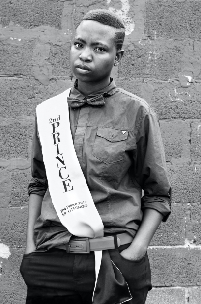 "A black-and-white photograph of a person standing against a wall wearing a white sash with the words ""2nd PRINCE"", ""2nd Prince 2012"", and ""Mr. UTHINGO"" in black font"