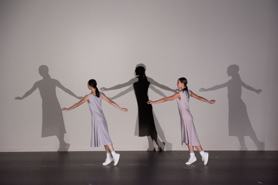 Two women in minimalist gray dresses and white sneakers dance onstage. Behind them three shadows echo their movement, of arms outstretches as in mid-stride.