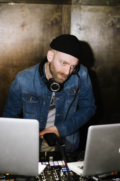 DJ Knife looking at his laptop monitor while he listens on his headphones.