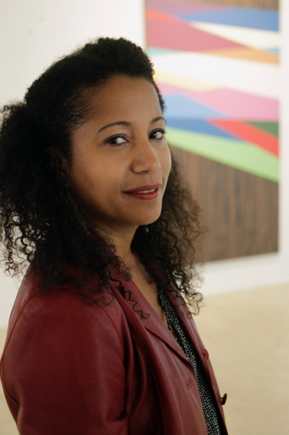 Headshot of Dell Marie Hamilton; a woman with medium skintone and a red jacket stands in front of an artwork (out of focus)