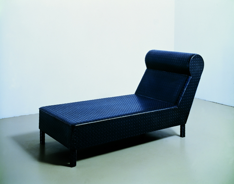 A sculpture made of a black steel tread plate shaped to form a long chaise.