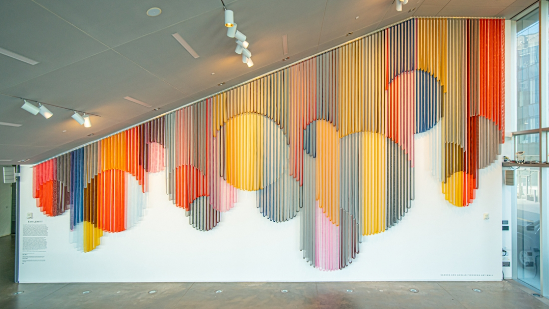 A monumental hanging wall sculpture made from bands of colorful coated mesh fabric which drape in various lengths to create series of interlocking circular forms, and installed in an empty spacious lobby.