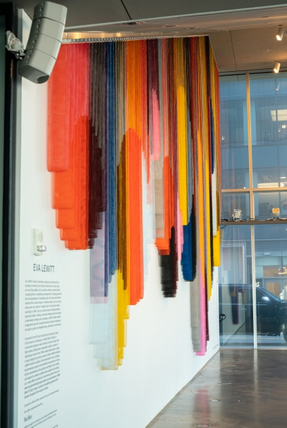 A side-angle view of a monumental hanging sculpture on a wall that's made up of bands of colorful coated mesh fabric which drape to create a series of interlocking circular forms, in an empty lobby space.