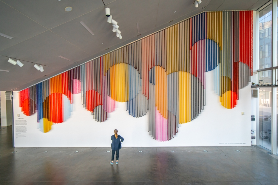 A visitor standing in an empty spacious lobby and looking up at a monumental hanging wall sculpture made from bands of colorful coated mesh fabric which drape in various lengths to create series of interlocking circular forms.