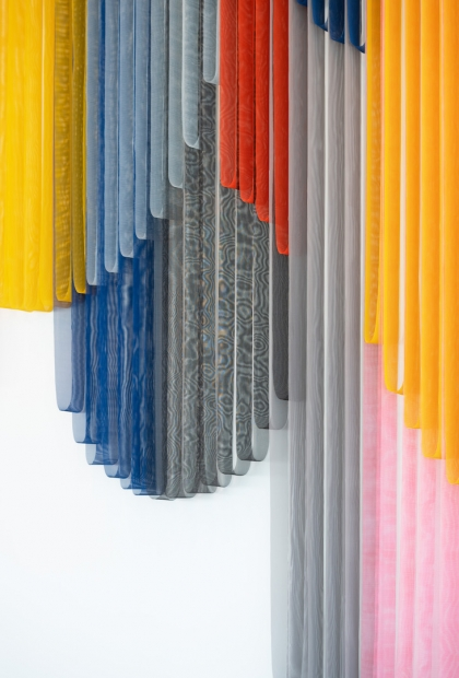 A close-up view of vibrant and colorful bands of coated mesh fabric hung and draped at various lengths.