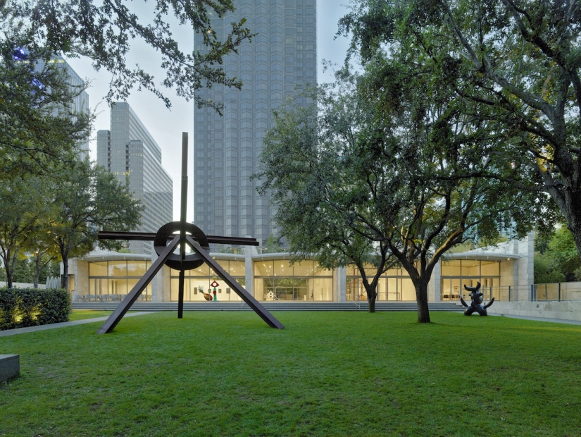 Two Modernist sculptures erected over the lawn and greenery in front of the building facade of the Nasher Sculpture Center.