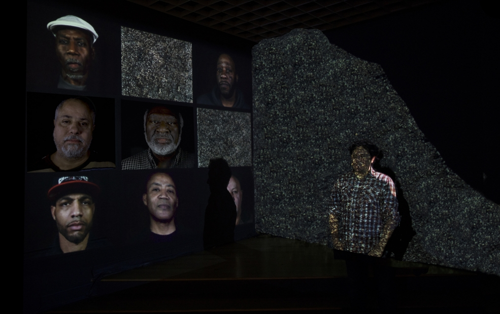 A grid of nine video screens on the left side of the image shows 7 close up portraits of men. Two screens show static. On the right side of the image, a man stands against a wall with his hands in his pockets. He is superimposed with a projection of static.